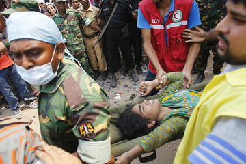 Rescue workers carry a survivor, who was trapped inside the rubble of the collapsed Rana Plaza building, in Savar