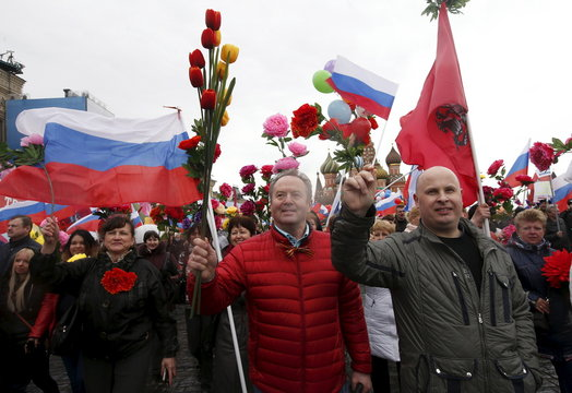 People walk with flags and artificial flowers at Red Square during May Day rally in Moscow