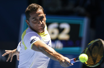 Nicolas Almagro of Spain hits a return to compatriot David Ferrer during their men's singles quarter-final match at the Australian Open tennis tournament in Melbourne