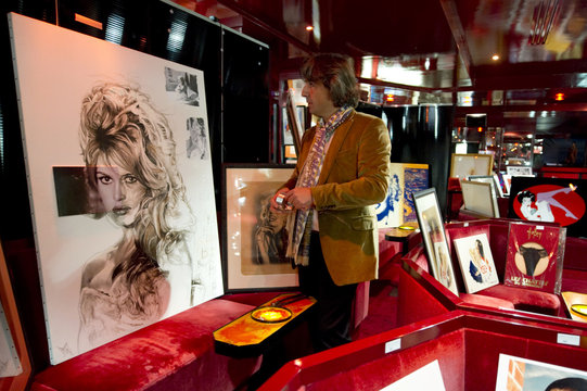"An employee looks at the painting ""BB le Mepris"" by Natacha Toutain at the Pin Up exhibition at Crazy Horse cabaret in Paris"