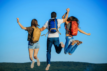 women and handsome man jumping on mountain top