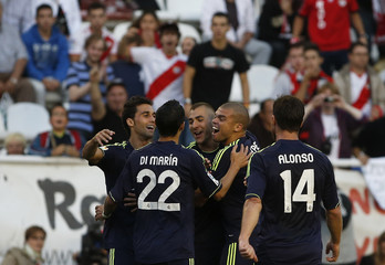 Real Madrid's Karim Benzema celebrates his goal with team mates during their Spanish First Division soccer match against Rayo Vallecano at Teresa Rivero stadium in Madrid