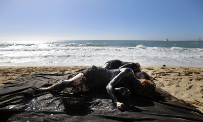 Activists lie on the beach with their bodies covered in black paint to resemble oil during a protest against oil prospection in the Mediterranean sea in Palma de Mallorca, in the Spanish Balearic island of Mallorca