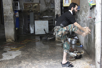 A Free Syrian Army fighter performs ablution before prayer on the frontline of the Salah al-Din neighbourhood in central Aleppo