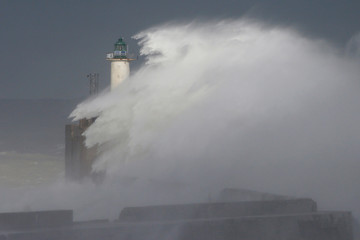 Waves crash against a lighthouse as the wind blows at around 120 kph (75mph), in Boulogne-sur-Mer