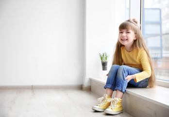 Little fashion girl sitting on window sill in light room