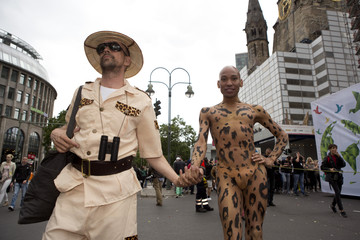 People dressed as a wild animal and a hunter participate in the annual Christopher Street Day parade on Kurfuerstendamm in Berlin