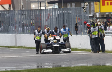 Track marshalls push Williams Formula One driver Maldonado after he slightly crashed against a protection wall during the qualifying session of the Canadian F1 Grand Prix at the Circuit Gilles Villeneuve in Montreal