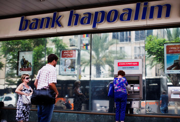 A woman uses an automated teller machine outside a Bank Hapoalim branch in Tel Aviv, Israel