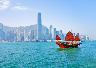 Deurstickers Hong-Kong View of Hong Kong skyline with a red Chinese sailboat passing on the Victoria Harbor in a sunny day.