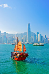 View of Hong Kong skyline with a red Chinese sailboat passing on the Victoria Harbor in a sunny day.