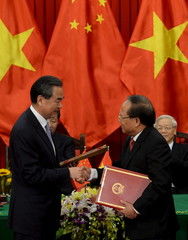 Wang exchanges signed documents with Anh in Hanoi