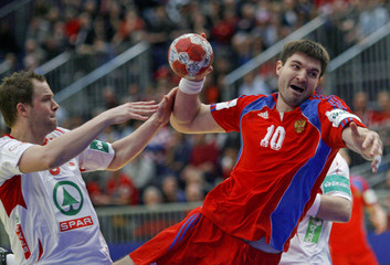 Russia's Chernoivanov attempts to score next to Strand Mamelund during their Men's European Handball Championship group A match in Graz