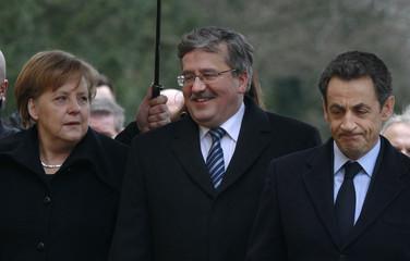 German Chancellor Merkel, French President Sarkozy and Polish President Komorowski walk to the Wilanow Palace