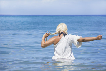 The woman of holidays, enjoying the sea in summer
