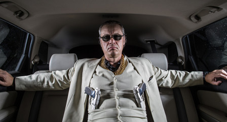Man in a white suit with a gun, ganster, mafia in the car - fototapety na wymiar