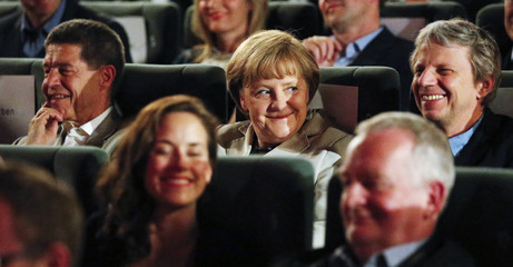 """German Chancellor Merkel, her husband and German film director Dresen wait for the screening of """"The Legend of Paul and Paula"""" at a cinema in Berlin"""