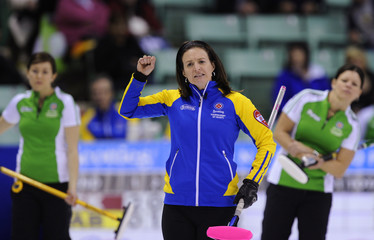 Alberta skip Nedohin reacts to her shot while Saskatchewan's Slywka and Materi watch from behind during their draw at the Scotties Tournament of Hearts curling championship in Red Deer