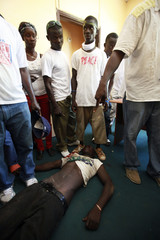 Supporters of presidential challenger Winston Tubman stand around the body of a comrade at the headquarters of the Congress for Democratic Change (CDC) after clashes with Liberian riot police in Monrovia
