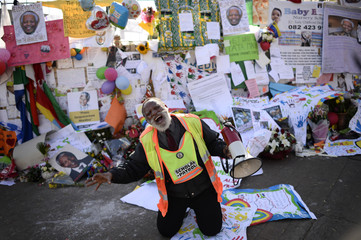A man prays for ailing former South African President Nelson Mandela outside the Medi-Clinic Heart Hospital where he is being treated in Pretoria