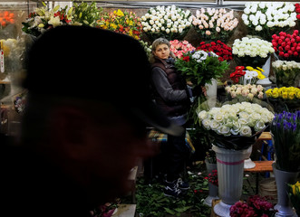 A woman waits for customers as she sells flowers at an underground walkway in Kiev