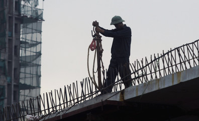 A man works at a construction site of a bridge in Hanoi