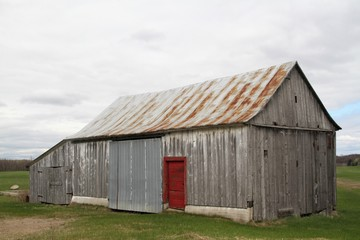 Old abandoned wood  barn with red door
