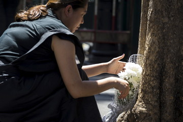 A woman lays down a bouquet of flowers near the Erawan shrine, the site of a deadly blast in central Bangkok