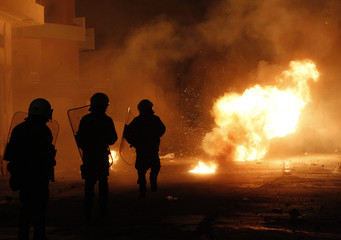 A petrol bomb explodes in front of riot policemen during clashes in the town of Keratea near Athens
