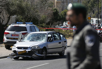 An Israeli border policeman stands near the car used by a Palestinian motorist to ram into a group of pedestrians in Jerusalem
