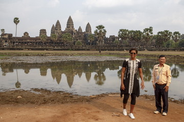 U.S. first lady Michelle Obama poses for a photograph with a tour guide at Angkor Wat temple in Siem Reap