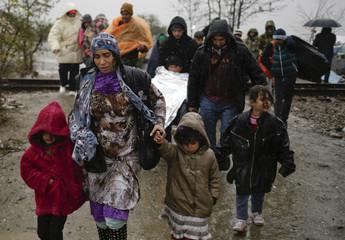 Migrants walk under rain after crossing the border from Greece into Macedonia, near Gevgelija