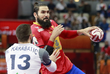 Maqueda of Spain is blocked by Nikola Karabatic of France during their semi-final match of the 24th Men's Handball World Championship in Doha