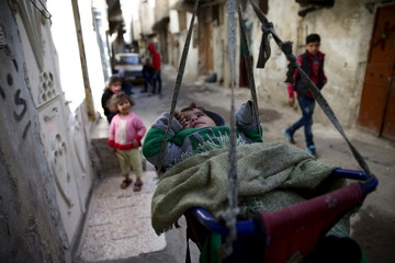 A child rests in a cradle along a street in the rebel-held Tishreen neighborhood of Damascus