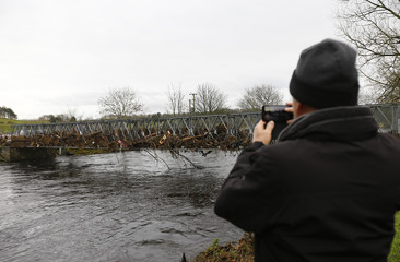 A man photographs a footbridge filled with debris following flooding at Newton Stewart in Scotland