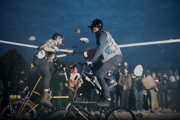"""Two men compete in a tall bike jousting event during """"Bike Kill 12"""" in the Brooklyn borough of New York City"""