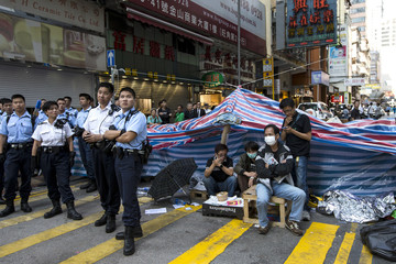 Police stand guard next to a barricade as pro-democracy protesters sit on it while bailiffs clear up one of the main streets under a court injunction at Mongkok shopping district in Hong Kong