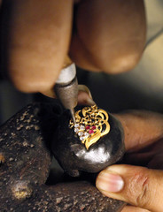 A jeweller sets stones in a gold pendant at a workshop in Lahore
