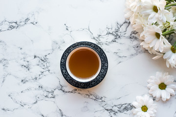 Top view of cup of tea and flowers on white marble background, flat lay