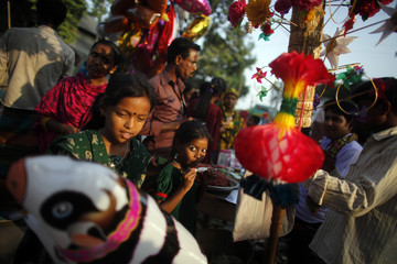 Vendors sell balloons and food as children hang around at a village fair in Manikganj