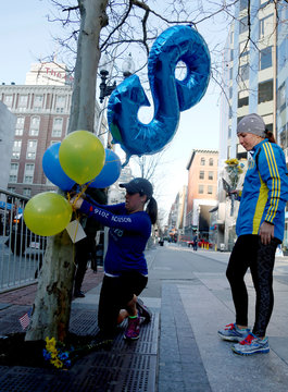Brooke Kelly, of Coventry, R.I., ties balloons to a tree as her friend Keegan Willette, looks on with flowers as they stop to remember Martin Richard on the anniversary of the Boston Marathon bombings on Boylston Street