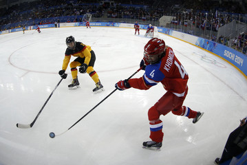 Russia's Khomich clears the puck past Germany's Kratzer during the first period of their women's ice hockey game at the 2014 Sochi Winter Olympics