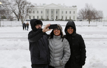 Australian tourists take a picture of themselves along Pennsylvania Ave.in front of the White House after the region was pounded with snow overnight around Washington