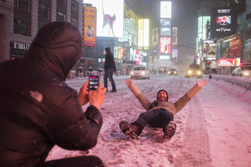 Valentin Borriello, from Paris, France, has his photograph made by a friend while lying on 7th Ave during snow storm in Times Square, New York