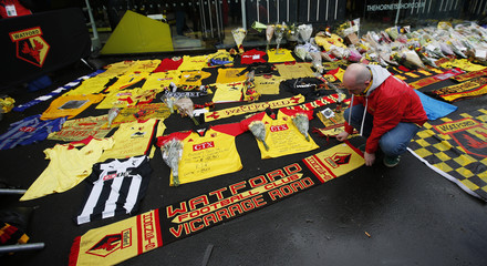 Fan adds a scarf to a tribute displayed in memory of the former England manager Graham Taylor before the match