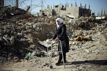 Palestinian girl Manar Al-Shinbari uses her walker near the ruins of her house that witnesses said was destroyed by Israeli shelling during the war, in Biet Hanoun