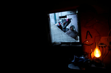 Palestinian woman stands in her house as a kerosene lamp lightens a dark room during a power cut in Beit Lahiya town in the northern Gaza Strip