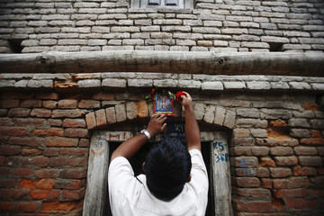 "A man sticks a picture of a snake god at the main entrance of his house and offers prayers to it to mark the ""Nag Panchami"" festival in Kathmandu"