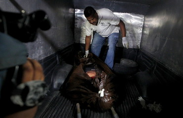 Forensic technician arranges the slain body of lawyer Montes Manzano in the coroner truck in Tegucigalpa