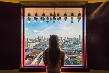 Tourist woman portrait standing backwards and looking at Bangkok City panorama with skyscrapers of business district from Golden Mountain Wat Saket view point, Thailand landscape